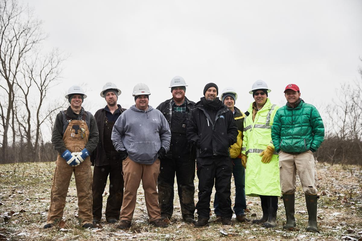 Photo caption:  Randall Gilbert of Save Our Monarch and 6 members of TransCanada's team pause for a picture in the pipeline rights-of-way with Gabe Karns.