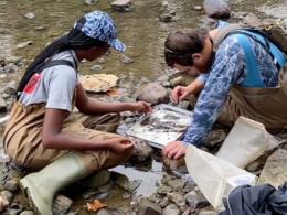 Two students sampling for macroinvertebrates.